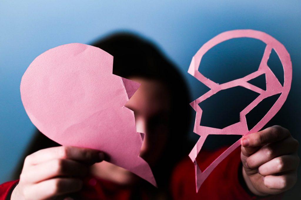 Femme tenant un cœur en papier rose, coeur brisé