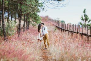 Couple heureux s'embrassant en promenade sur un chemin fleuri