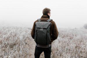 Homme de dos habillé chaudement, avec un sac à dos, dans un champs givré du matin