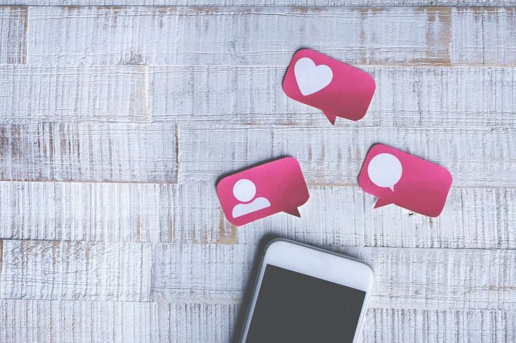 Téléphone type Iphone avec les icones des réseaux sociaux, like, commentaire et j'aime