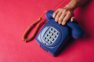 Main posée sur un téléphone sur un fond rose, Téléphone Rose