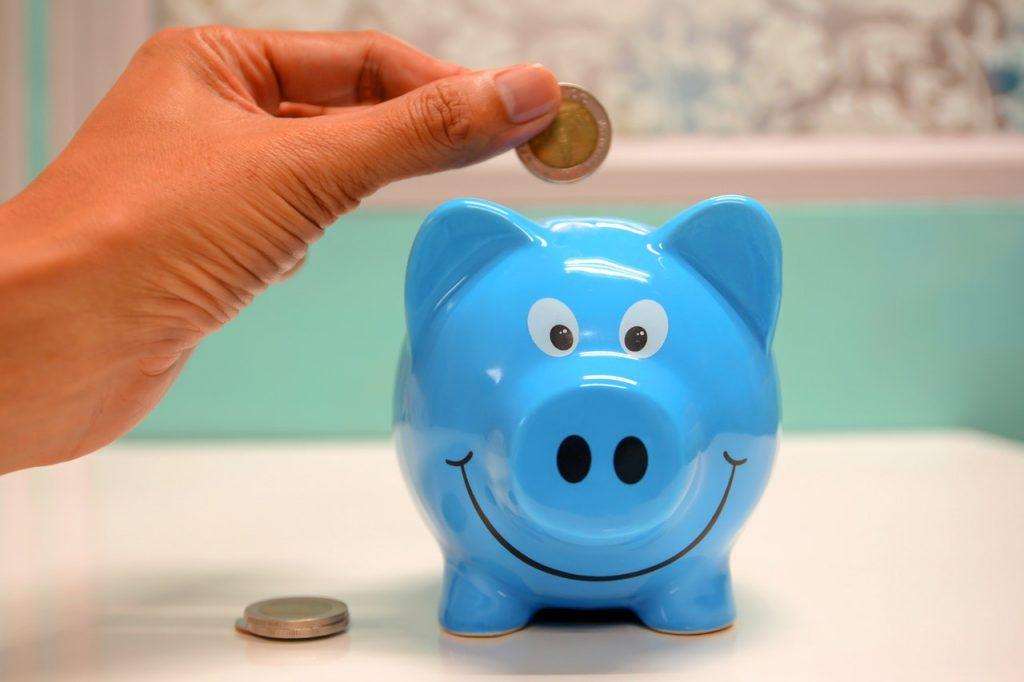 Tirelire cochon bleu souriant, main mettant monnaie à l'intérieur