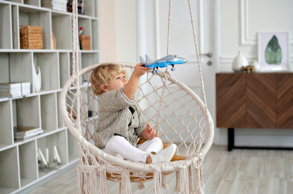 Enfant assis sur un fauteuil suspendue jouant avec un avion