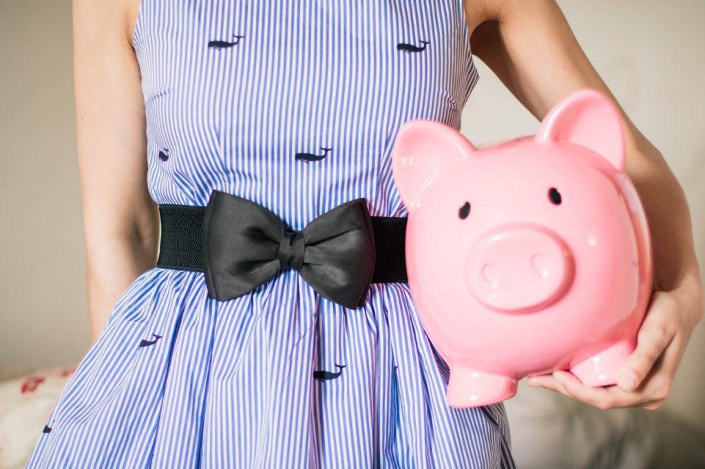 Femme en robe portant une tirelire cochon