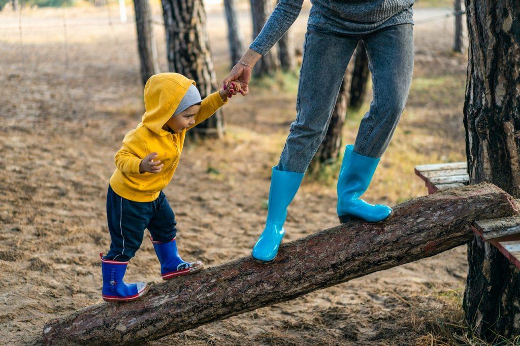 Enfant grimpant sur un arbre portant ciré et botte de pluie  tenant la main d'un adulte