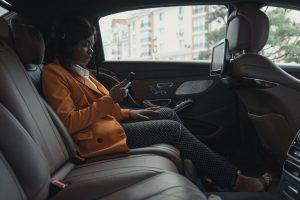 Femme assise dans une voiture se faisant conduire