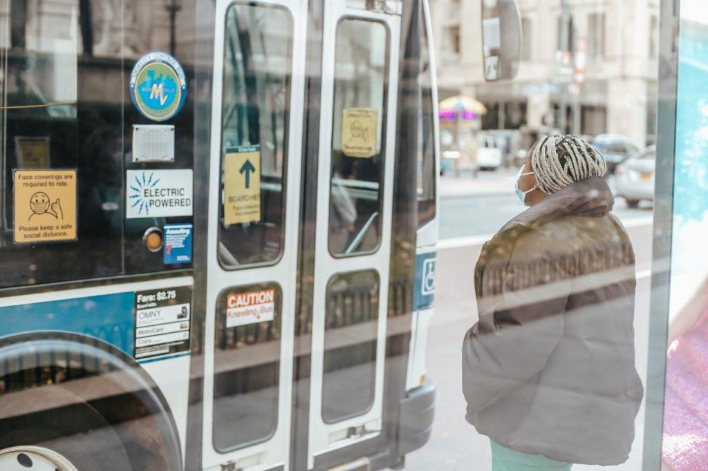 Femme attendant devant la porte d'un bus