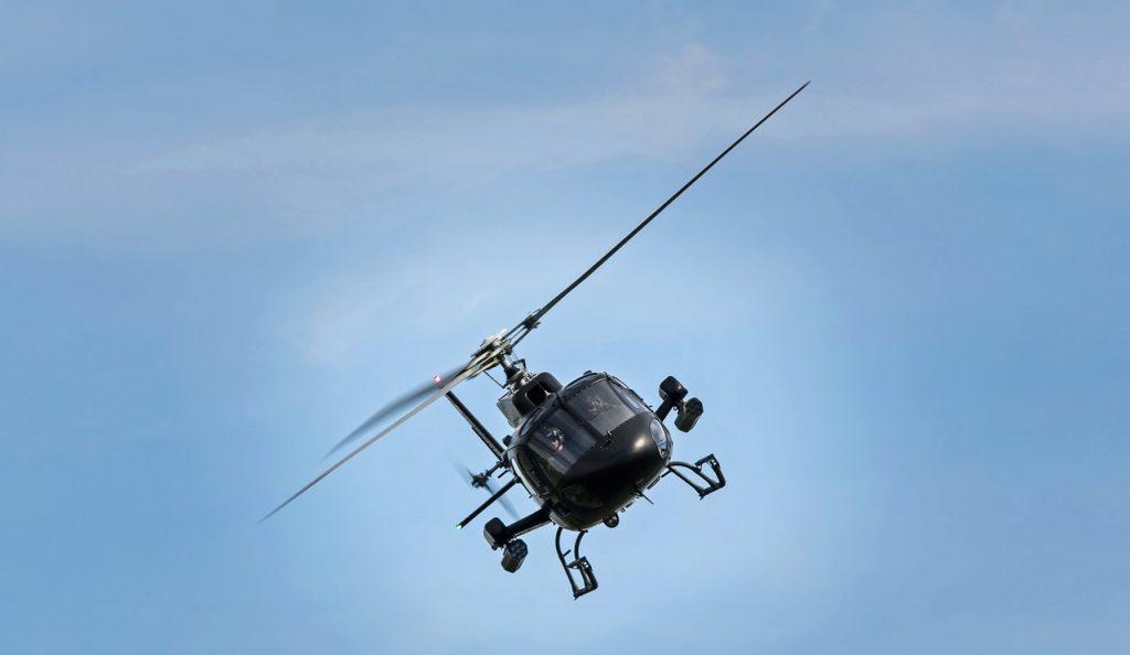 Hélicoptère noir volant dans le ciel bleu