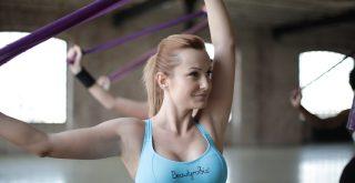Femme dans une salle de sport faisant exercice avec bande élastique