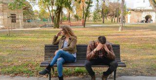 Couple se disputant, assis sur un banc, triste et en colère